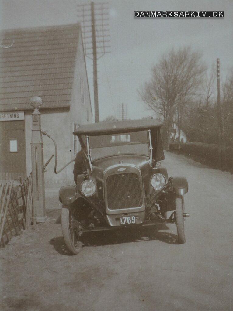 En Chevrolet får fyldt tanken fra Lobbæk Cykleforretnings Shell stander - 1923
