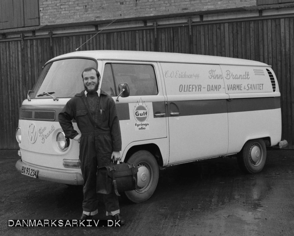 En glad blikkenslager poserer foran sin værkstedsvogn - Volkswagen Transporter fra Finn Brandt